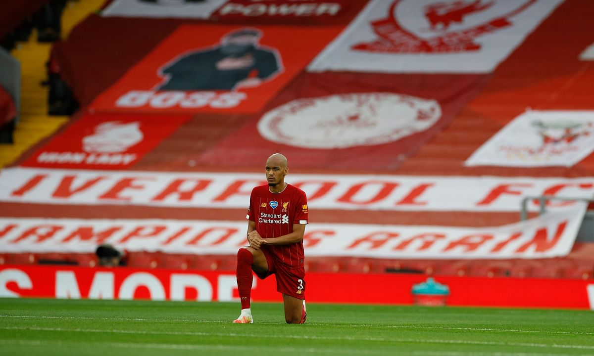 Liverpool's Fabinho takes a knee just prior to the start of the English Premier League soccer match between Liverpool and Chelsea at Anfield Stadium in Liverpool, England, Wednesday, July 22, 2020.