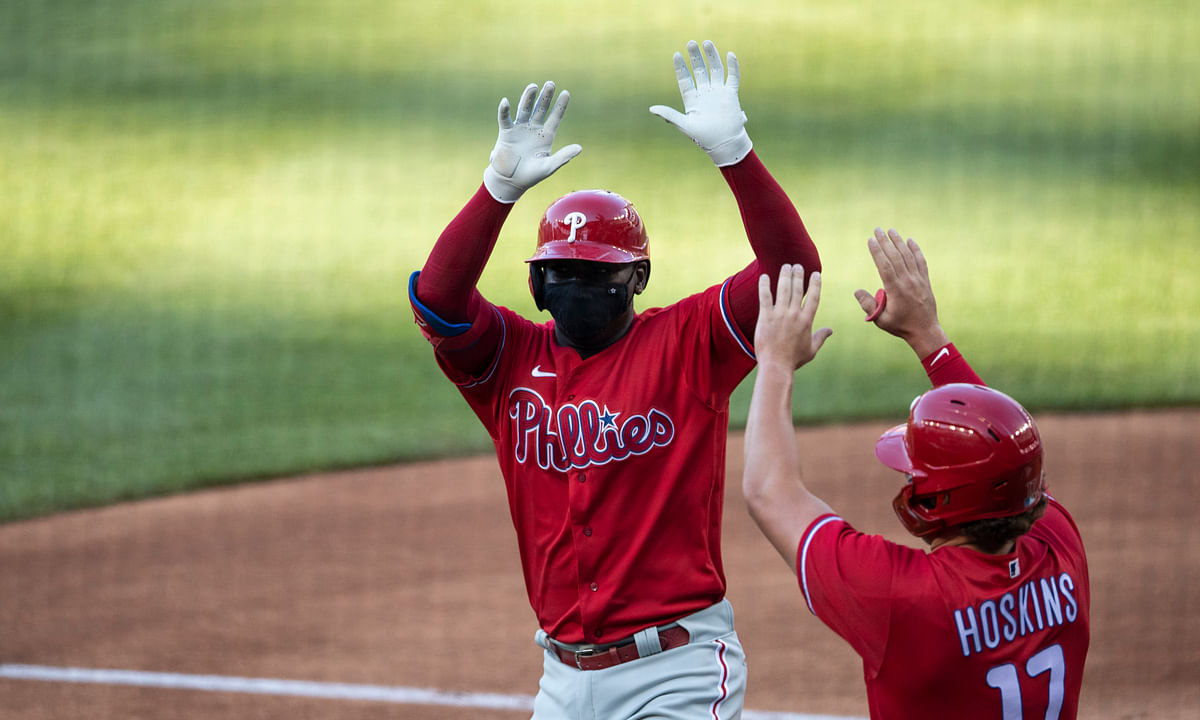 Philadelphia Phillies' Didi Gregorius celebrates without touching, while wearing a mask, his three-run homer with Rhys Hoskins during the first inning of an exhibition baseball game against the Washington Nationals at Nationals Park, Saturday, July 18, 2020, in Washington.