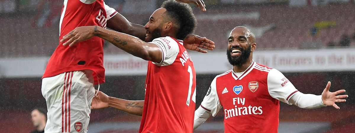 Arsenal's Pierre-Emerick Aubameyang, centre, is congratulated by teammates after scoring his team's first goal during the English Premier League soccer match between Arsenal and Leicester at Emirates Stadium in London, England, Tuesday, July 7, 2020.