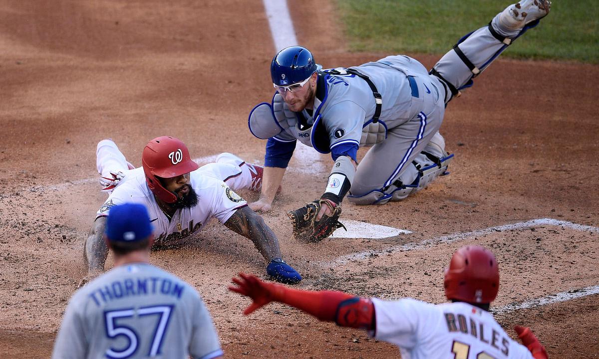 Washington Nationals' Eric Thames, left, slides past Toronto Blue Jays catcher Danny Jansen, right, while scoring on a double by Kurt Suzuki during the fourth inning of a baseball game Monday, July 27, 2020, in Washington. Watching are Nationals' Victor Robles (16) and Blue Jays starting pitcher Trent Thornton (57).