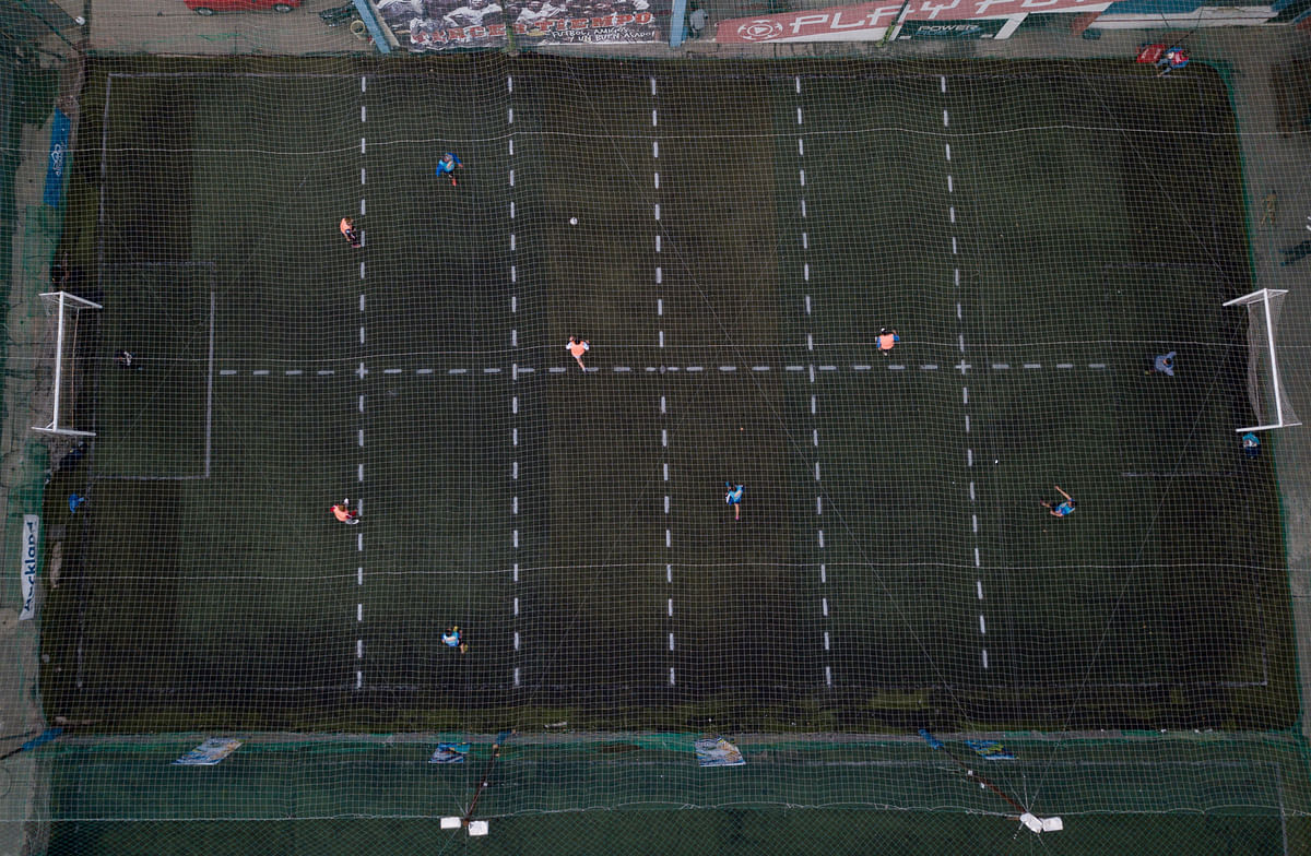 Men play soccer at a local club, Play Futbol 5, in Pergamino, Argentina, Wednesday, July 1, 2020. In order to continue playing amid government restrictions to curb the spread of the new coronavirus, the club divided its soccer field into 12 rectangles to mark limited areas for each player, keeping them from making physical contact.