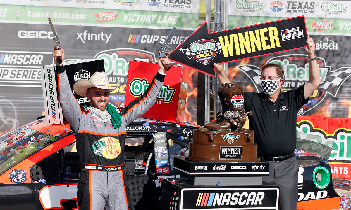 "Texas Motor Speedway President and General Manager Eddie Gossage, right, holds a ""winner"" sign as Austin Dillon, left, celebrates by firing six shooters after winning the NASCAR Cup Series auto race at Texas Motor Speedway in Fort Worth, Texas, Sunday, July 19, 2020."