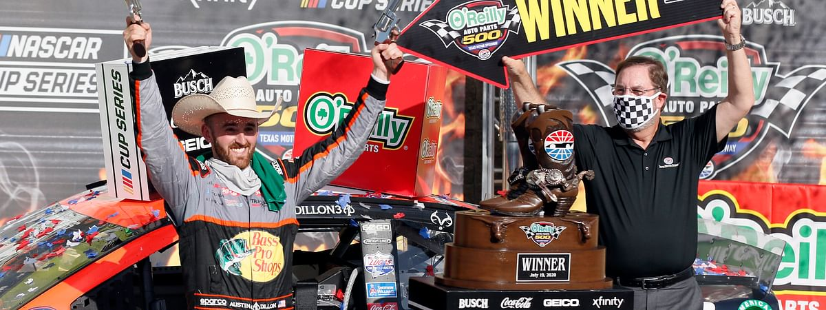 """Texas Motor Speedway President and General Manager Eddie Gossage, right, holds a """"winner"""" sign as Austin Dillon, left, celebrates by firing six shooters after winning the NASCAR Cup Series auto race at Texas Motor Speedway in Fort Worth, Texas, Sunday, July 19, 2020."""