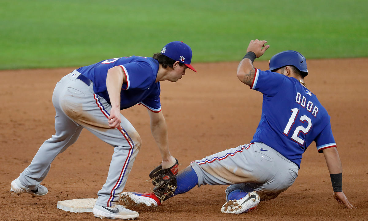 Texas Rangers second baseman Nick Solak, left, tags out Rougned Odor on a stolen base-attempt during an intrasquad practice baseball game at Globe Life Field in Arlington, Texas, Monday, July 6, 2020.