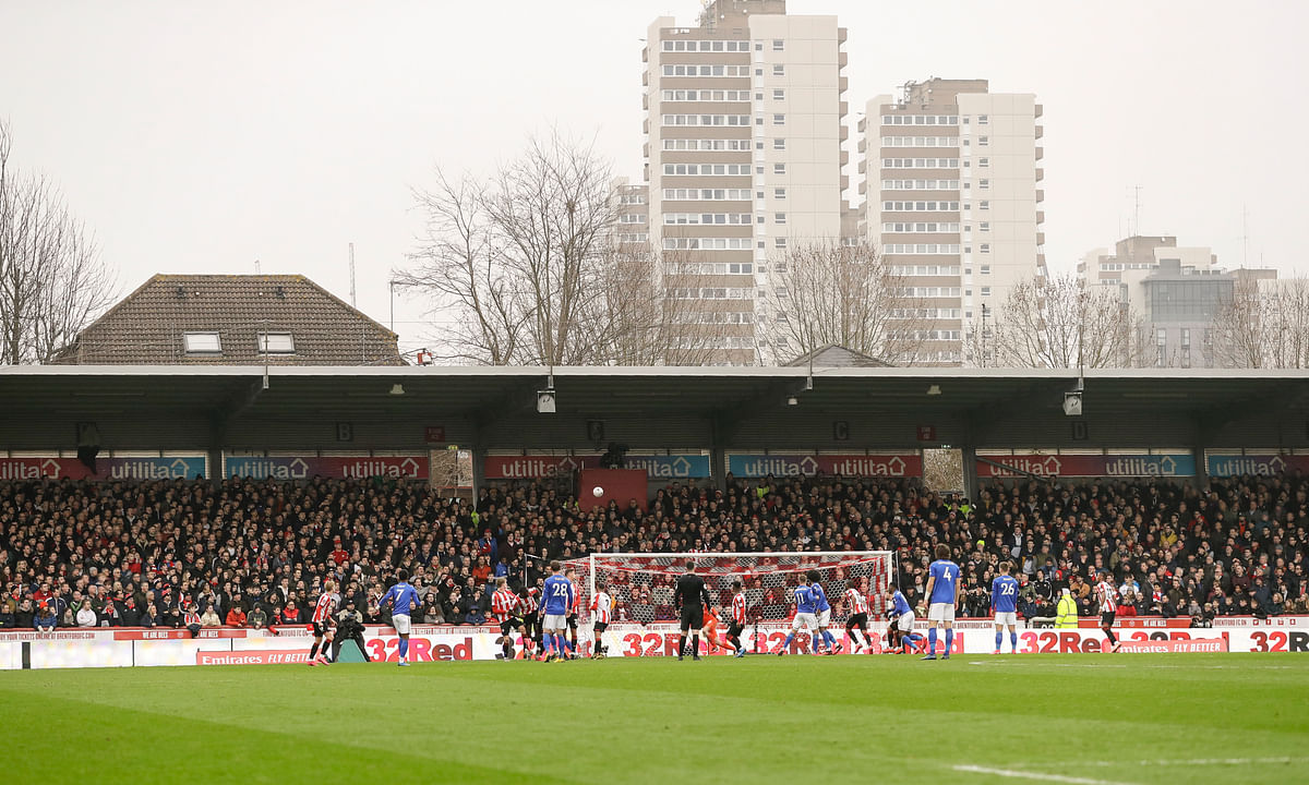 In this Saturday, Jan. 25, 2020 file photo, spectators watch from the stands of Griffin Park stadium, inaugurated in 1904, during the English FA Cup fourth round soccer match between Brentford FC and Leicester City at Griffin Park stadium in London.