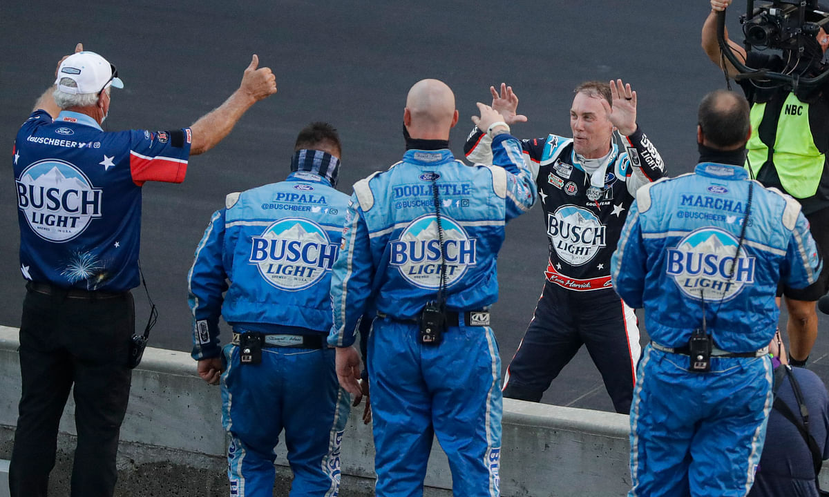 Kevin Harvick, on far side of wall, celebrates with his crew after winning the NASCAR Cup Series auto race at Indianapolis Motor Speedway in Indianapolis, Sunday, July 5, 2020. (AP Photo/Darron Cummings)