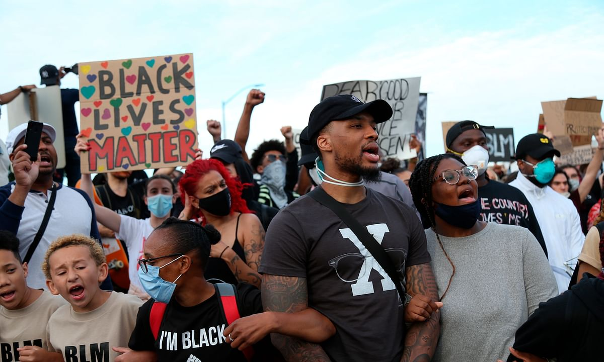 Portland Trailblazers' Damian Lillard, second from right, joins other demonstrators in Portland, Ore., during a protest against police brutality and racism sparked by the death of George Floyd, who died May 25 after being restrained by police in Minneapolis.