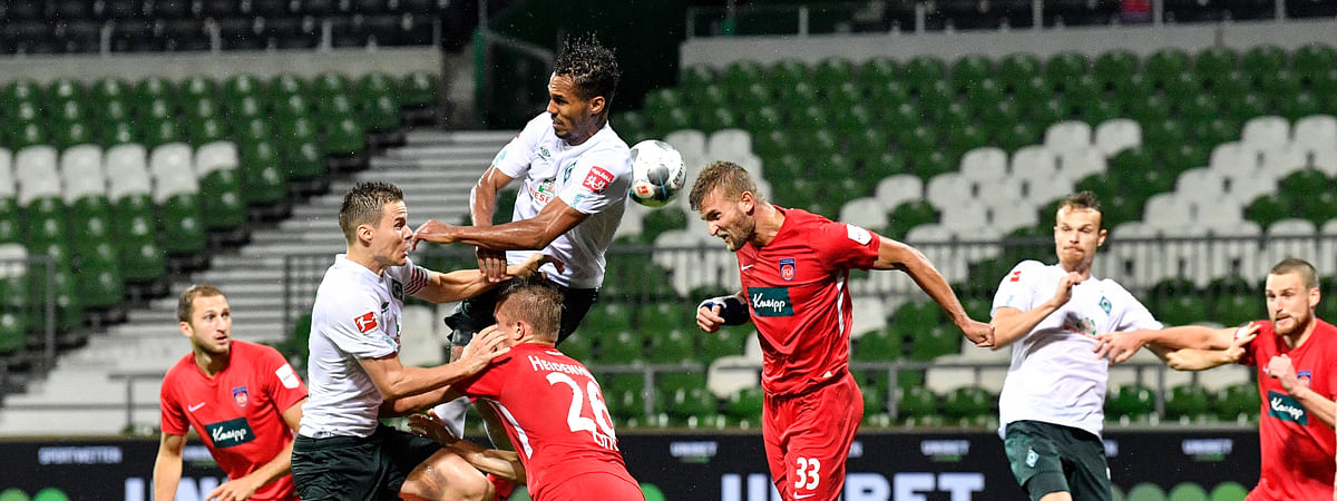 Bremen's Theodor Gebre Selassie, up, and Heidenheim's Timo Beermann, center, challenge for the ball during the German Bundesliga relegation first leg soccer match between Werder Bremen and 1. FC Heidenheim in Bremen, Germany, Thursday, July 2, 2020. Because of the coronavirus outbreak all soccer matches of the German Bundesliga take place without spectators.