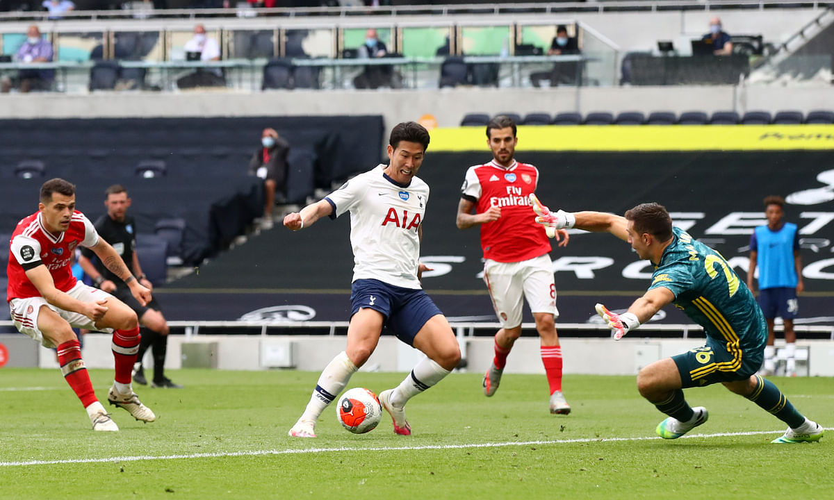 Tottenham's Son Heung-min, center, attempts and fails to score past Arsenal's goalkeeper Emiliano Martinez, right, during the English Premier League soccer match between Tottenham Hotspur and Arsenal at the Tottenham Hotspur Stadium in London, England, Sunday, July 12, 2020.