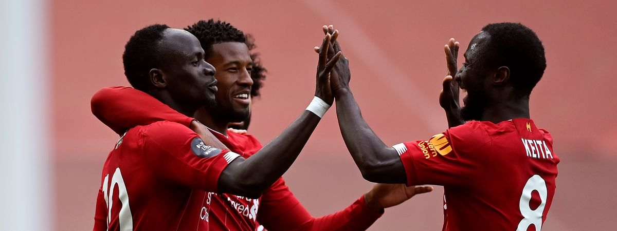 Liverpool's Sadio Mane, left, celebrates after scoring the opening goal during the English Premier League soccer match between Liverpool and Aston Villa at Anfield Stadium in Liverpool, England, Sunday, July 5, 2020.