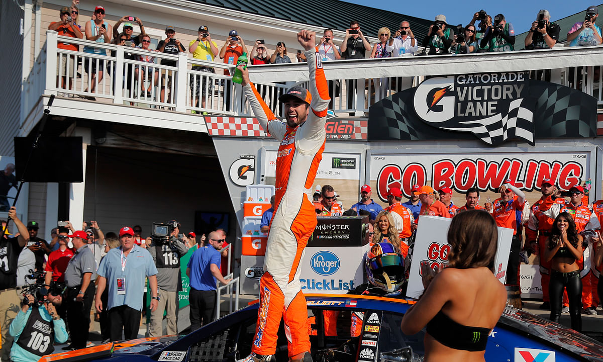 """In this Aug. 5, 2018, file photo, Chase Elliott, center, celebrates after winning a NASCAR Cup Series auto race in Watkins Glen, N.Y. Three months after its opening day was canceled by the coronavirus pandemic, Watkins Glen International is hosting car clubs again as NASCAR weekend looms in mid-August. """"Everybody is excited about getting back in the saddle. I know we are,"""" track president Michael Printup said."""