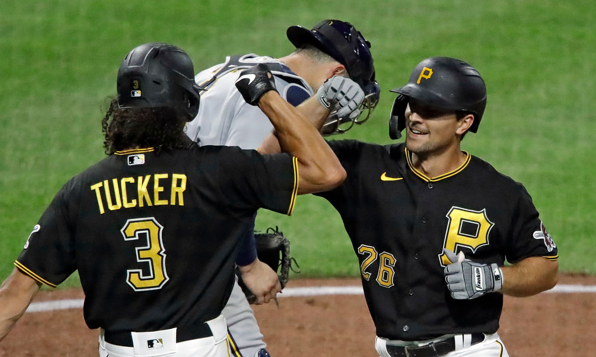Pittsburgh Pirates' Adam Frazier (26) celebrates with Cole Tucker (3) as he crosses home plate in front of Milwaukee Brewers catcher Manny Pina after hitting a two-run home run off relief pitcher Bobby Wahl during the eighth inning of an baseball game in Pittsburgh, Tuesday, July 28, 2020.