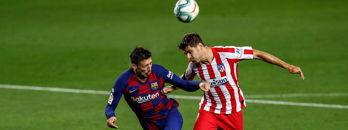 Barcelona's Clement Lenglet, left, and Atletico Madrid's Alvaro Morata jump for the ball during the Spanish La Liga soccer match between FC Barcelona and Atletico Madrid at the Camp Nou stadium in Barcelona, Spain, Tuesday, June 30, 2020.