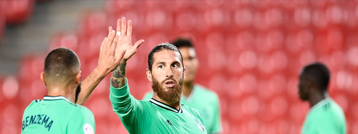 Real Madrid's Sergio Ramos, center, gestures with his teammate Benzema during the Spanish La Liga soccer match between Granada and Real Madrid at the Los Carmenes stadium in Granada, Spain, Monday, July 13, 2020.