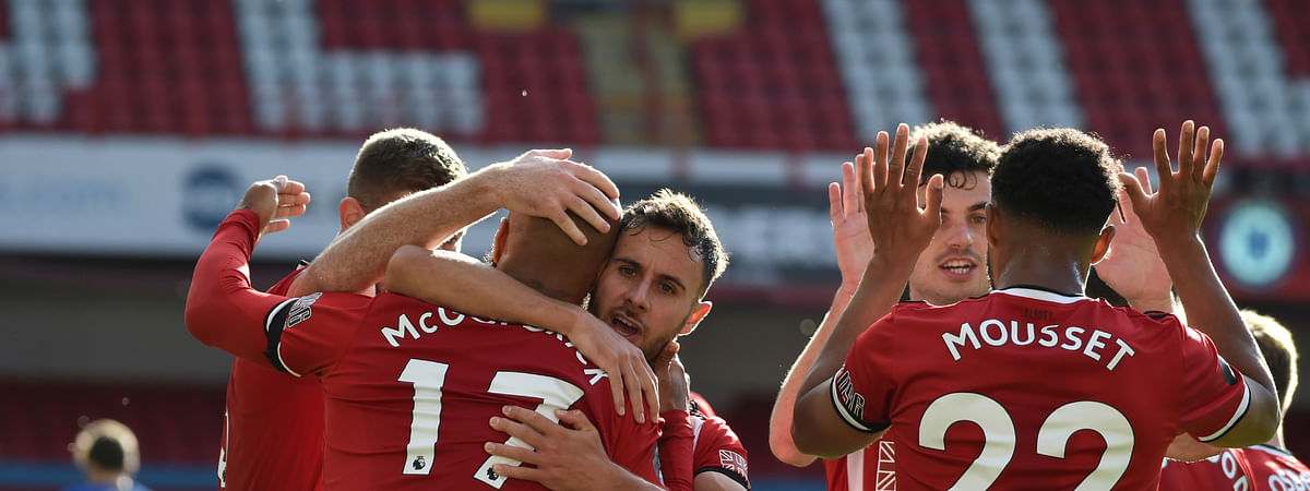 Sheffield United's David McGoldrick, left, celebrates after scoring his side's third goal during the English Premier League soccer match between Sheffield United and Chelsea at Bramall Lane in Sheffield, England, Saturday, July 11, 2020.