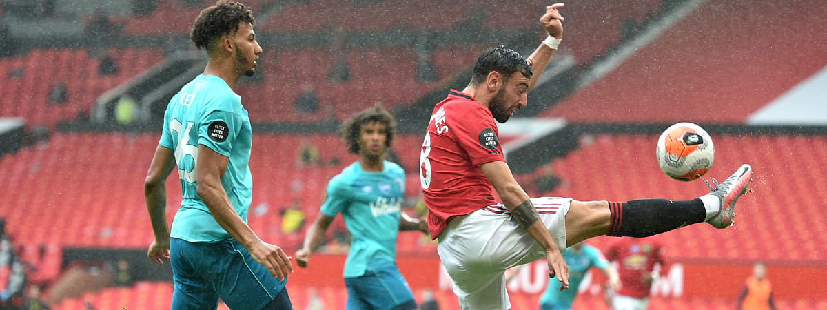 Manchester United's Bruno Fernandes, right, reaches for the ball while Bournemouth's Lloyd Kelly, left, defends during the English Premier League soccer match between Manchester United and Bournemouth at Old Trafford stadium in Manchester, England, Saturday, July 4, 2020.
