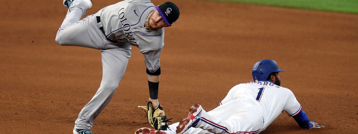 Colorado Rockies shortstop Trevor Story (27) makes the tag on Texas Rangers' Elvis Andrus (1) who was attempting to steal in the fourth inning of a baseball game Saturday, July 25, 2020, in Arlington, Texas.