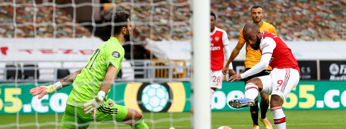 Arsenal's Alexandre Lacazette scores his side's second goal past Wolverhampton Wanderers' goalkeeper Rui Patricio, left, during the English Premier League soccer match between Wolverhampton Wanderers and Arsenal at the Molineux Stadium in Wolverhampton, England, Saturday, July 4, 2020.