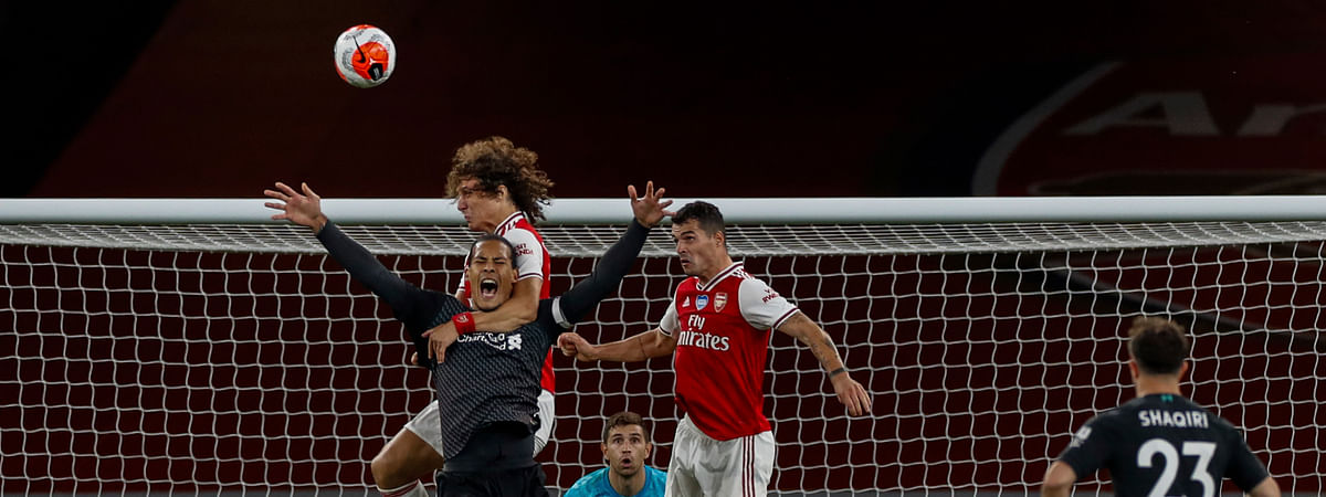 Arsenal's David Luiz grabs Liverpool's Virgil van Dijk, foreground and left, during the English Premier League soccer match between Arsenal and Liverpool at the Emirates Stadium in London, England, Wednesday, July 15, 2020.