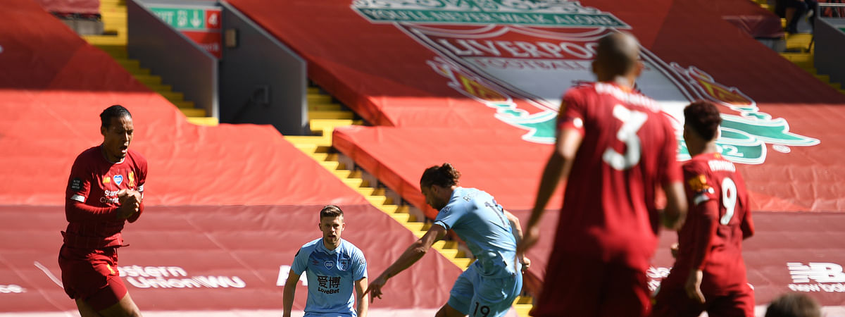 Burnley's Jay Rodriguez, center, shoots and scores his sides first goal during the English Premier League soccer match between Liverpool and Burnley at Anfield, Liverpool, England, Saturday, July 11, 2020.