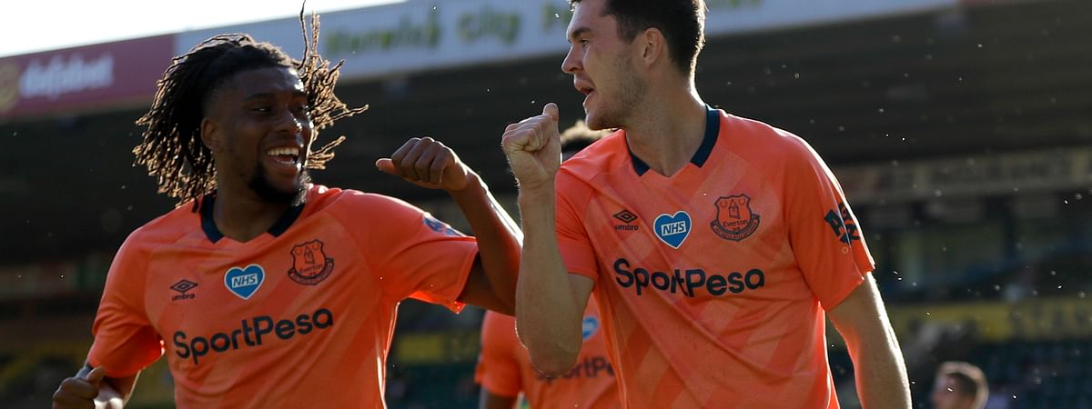 Everton's Michael Keane, right, and Everton's Alex Iwobi celebrate scoring their side's first goal during the English Premier League soccer match between Norwich and Everton at Carrow Road Stadium in Norwich, England, Wednesday, June 24, 2020.
