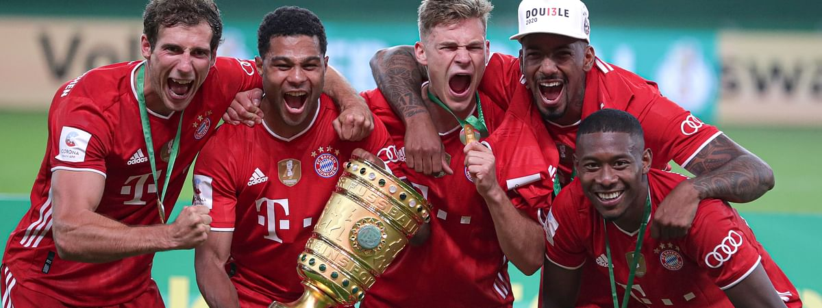 Bayern Munich players celebrate with the trophy after winning the German soccer cup (DFB Pokal) final match between Bayer 04 Leverkusen and FC Bayern Munich in Berlin, Germany, Saturday, July 4, 2020.