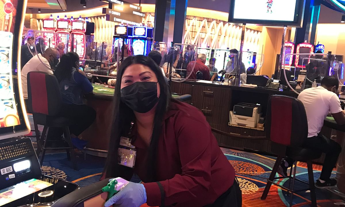 An employee of Rivers Casino in Philadelphia cleans the machines