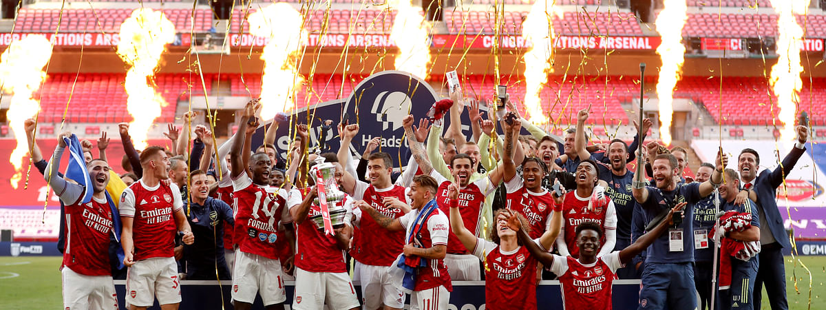 Pyrotechnics go off as Arsenal's players celebrate with the trophy after the FA Cup final soccer match between Arsenal and Chelsea at Wembley stadium in London, England, Saturday, Aug.1, 2020.