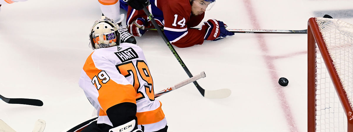 Montreal Canadiens center Nick Suzuki (14) fails to connect with the puck as Philadelphia Flyers goaltender Carter Hart (79) defends the net during the second period of Game 3 of an NHL hockey playoff first-round series Sunday, Aug. 16, 2020, in Toronto.