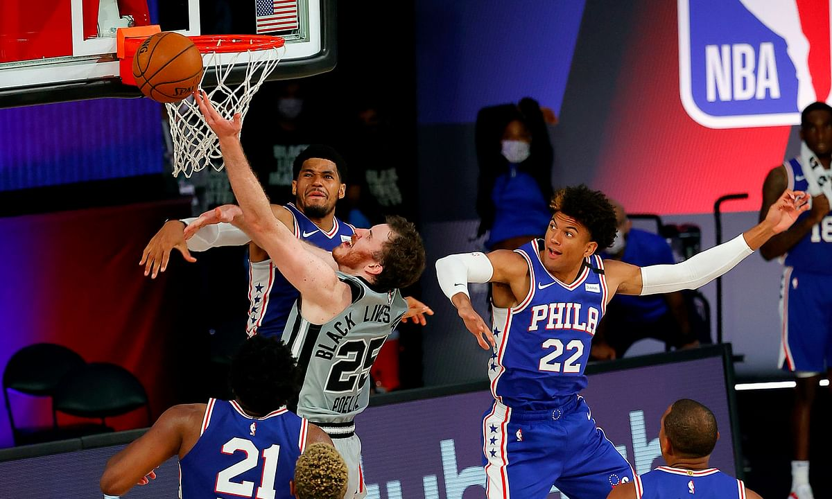 Sixers Tobias Harris and Matisse Thybulle (22) defend against the Spurs' Jakob Poeltl (25) as Joel Embiid watches Monday