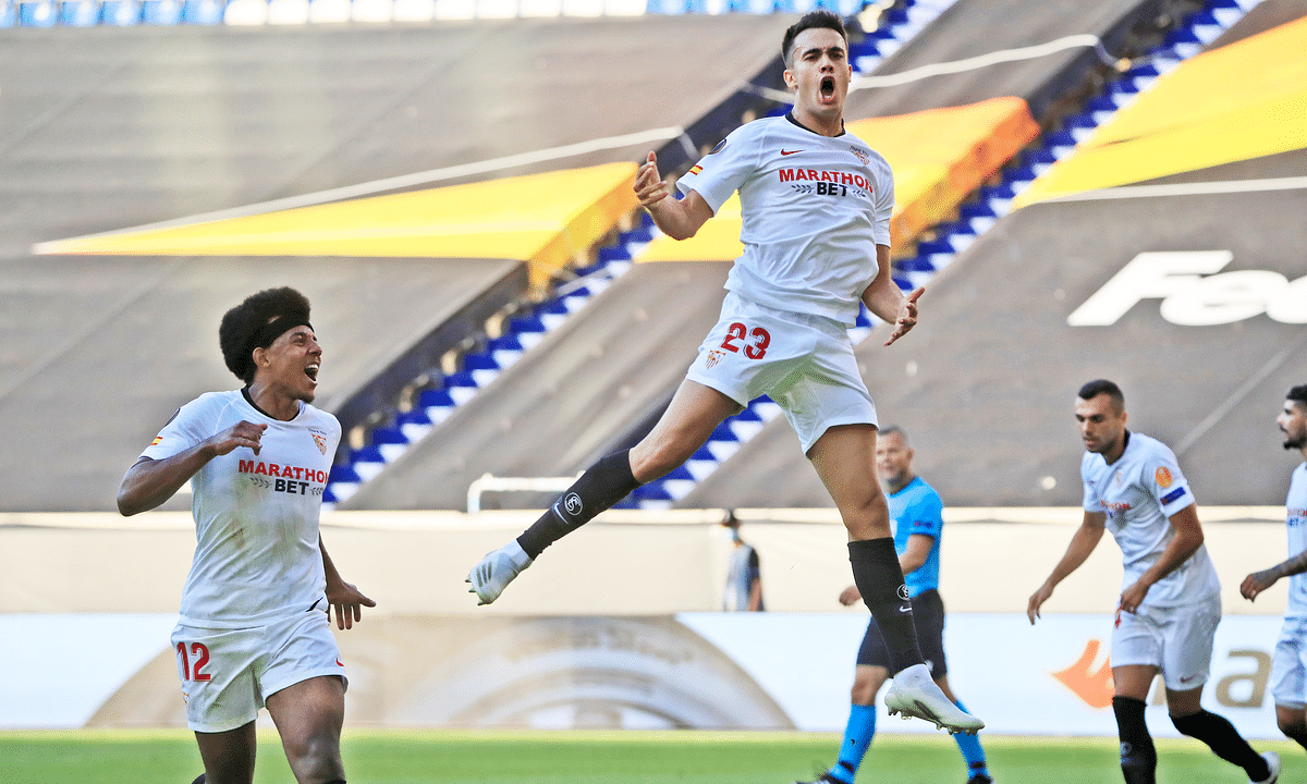 Sevilla's Sergio Reguilon, right, celebrates after scoring his side's first goal during the Europa League, round of 16 soccer match between Roma and Sevilla, at the Schauinsland-Reisen-Arena in Duisburg, Germany, Thursday, Aug. 6, 2020.