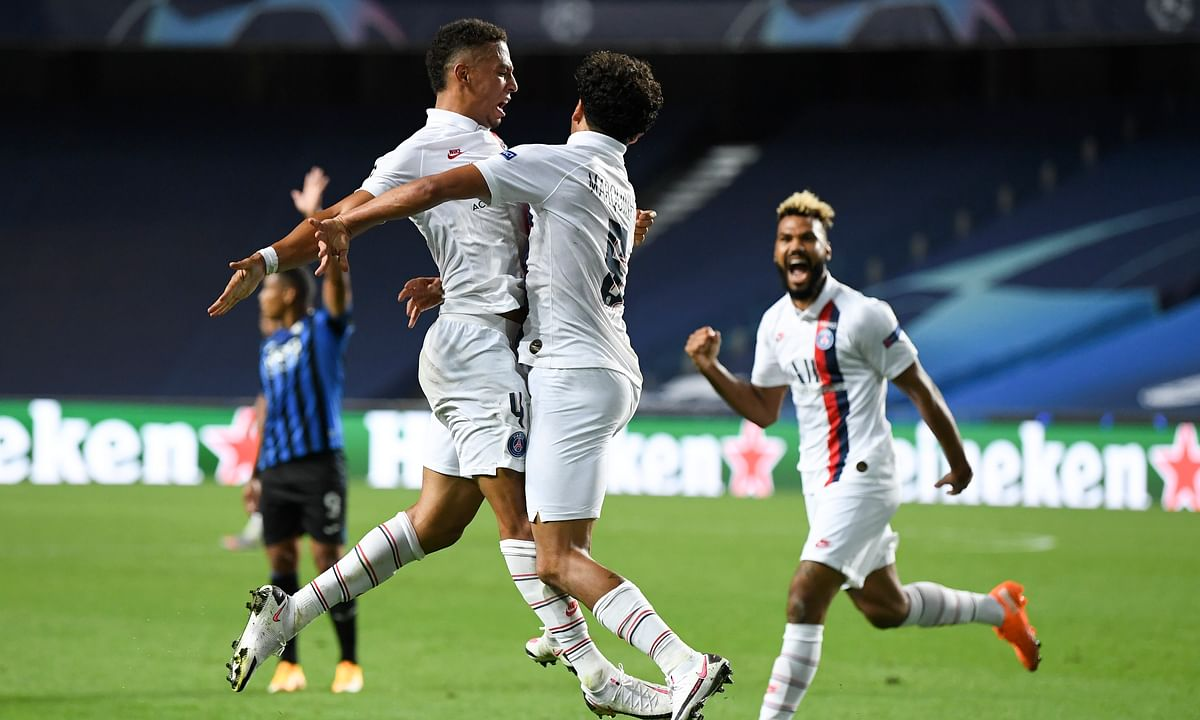 PSG's Marquinhos, centre, celebrates with teammate Thilo Kehrer, left, after scoring his team's first goal during the Champions League quarterfinal match between Atalanta and PSG at Luz stadium, Lisbon, Portugal, Wednesday, Aug. 12, 2020.