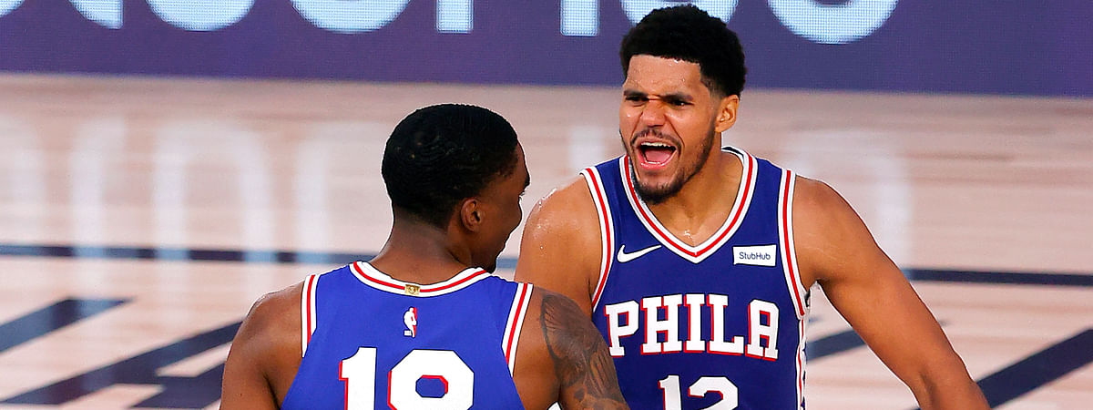 Philadelphia 76ers Shake Milton (18) is congratulated by his teammate, Tobias Harris (12), after scoring a three point basket against the San Antonio Spurs during the second half of an NBA basketball game Monday, Aug. 3, 2020, in Lake Buena Vista, Fla.