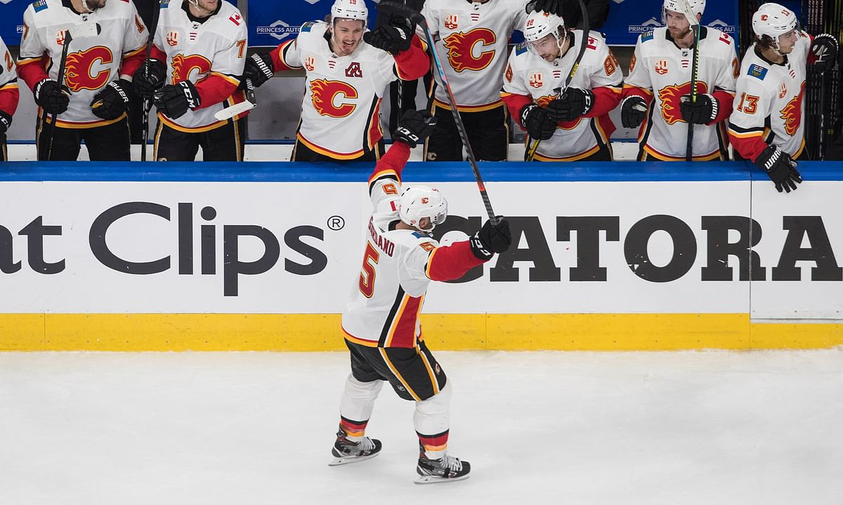 Calgary Flames' Mark Giordano (5) celebrates an empty-net goal with teammates against the Winnipeg Jets during the third period of an NHL qualifying round game, in Edmonton, Alberta, Thursday, Aug. 6, 2020.