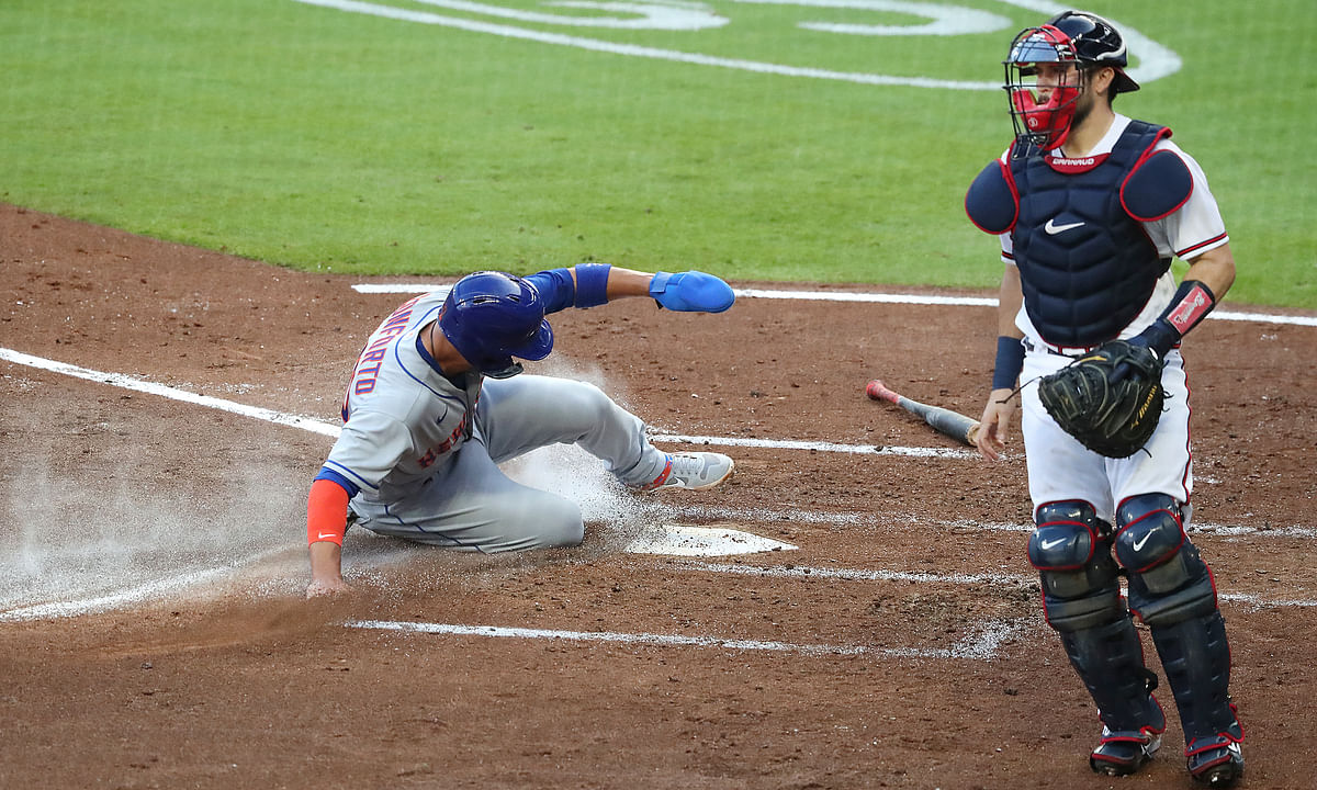 New York Mets' Michael Conforto scores past Atlanta Braves catcher Travis D'Arnaud on a single by Robinson Cano during the third inning of a baseball game Monday, Aug. 3, 2020,, in Atlanta.