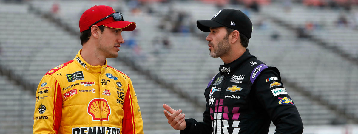 FILE - In this March 29, 2019, file photo, Jimmie Johnson, right, chats with Joey Logano before qualifying for the NASCAR Cup Series auto race at Texas Motor Speedway in Fort Worth, Texas. The final three playoff spots are up for grabs as stock-car racing returns to the high-banked superspeedway in Daytona Beach, Fla., two weeks after running the road course. Nearly half the field is looking to clinch a postseason berth with a victory, including seven-time series champion Jimmie Johnson.