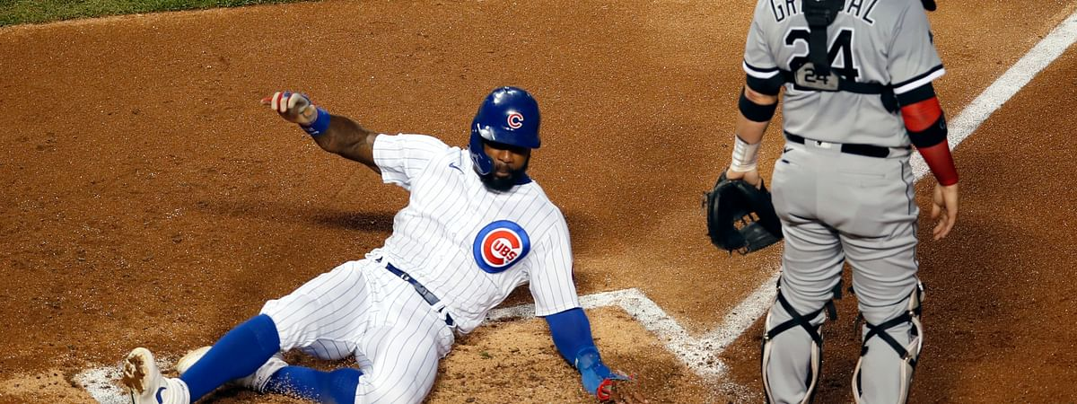 Chicago Cubs' Jason Heyward, left, slides into home plate past Chicago White Sox catcher Yasmani Grandal (24) on a two-RBI double off the bat of teammate Victor Caratini during the second inning of a baseball game Saturday, Aug. 22, 2020, in Chicago.