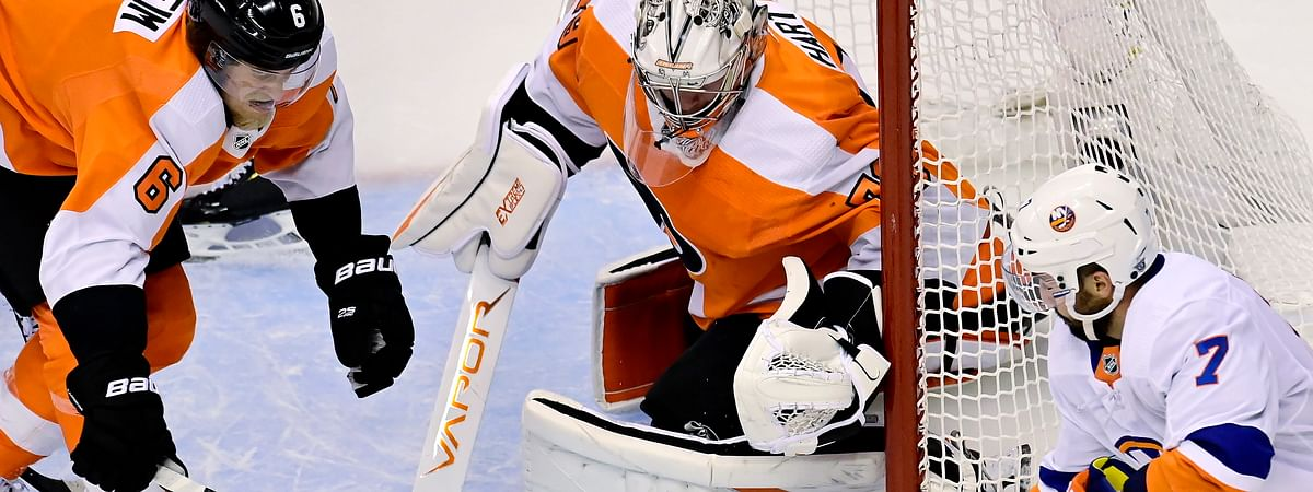 Philadelphia Flyers goaltender Carter Hart (79) makes a save as teammate Travis Sanheim (6) and New York Islanders right wing Jordan Eberle (7) vie for the rebound during first-period NHL Stanley Cup Eastern Conference playoff hockey game action in Toronto, Monday, Aug. 24, 2020.