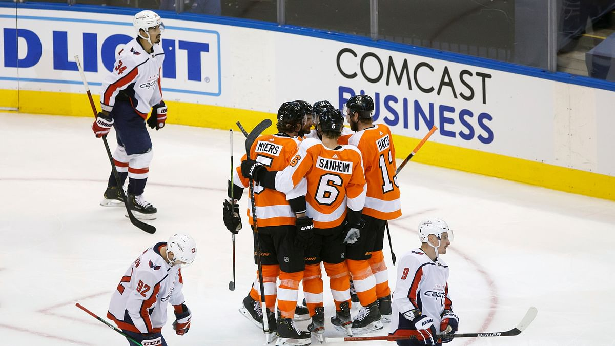 Philadelphia Flyers center Scott Laughton (21) celebrates his goal alongside teammates Travis Konecny (11), Kevin Hayes (13) Travis Sanheim (6) and Philippe Myers (5) during the third period of an NHL hockey playoff game Thursday, Aug. 6, 2020, in Toronto.