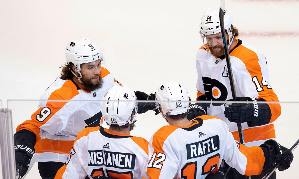 Philadelphia Flyers left wing Michael Raffl (12) is congratulated by teammates defensemen Ivan Provorov (9) and Matt Niskanen (15) and center Sean Couturier (14) after scoring on the Montreal Canadiens during the first period of an NHL hockey Eastern Conference Stanley Cup first round playoff game in Toronto on Tuesday, Aug. 18, 2020.