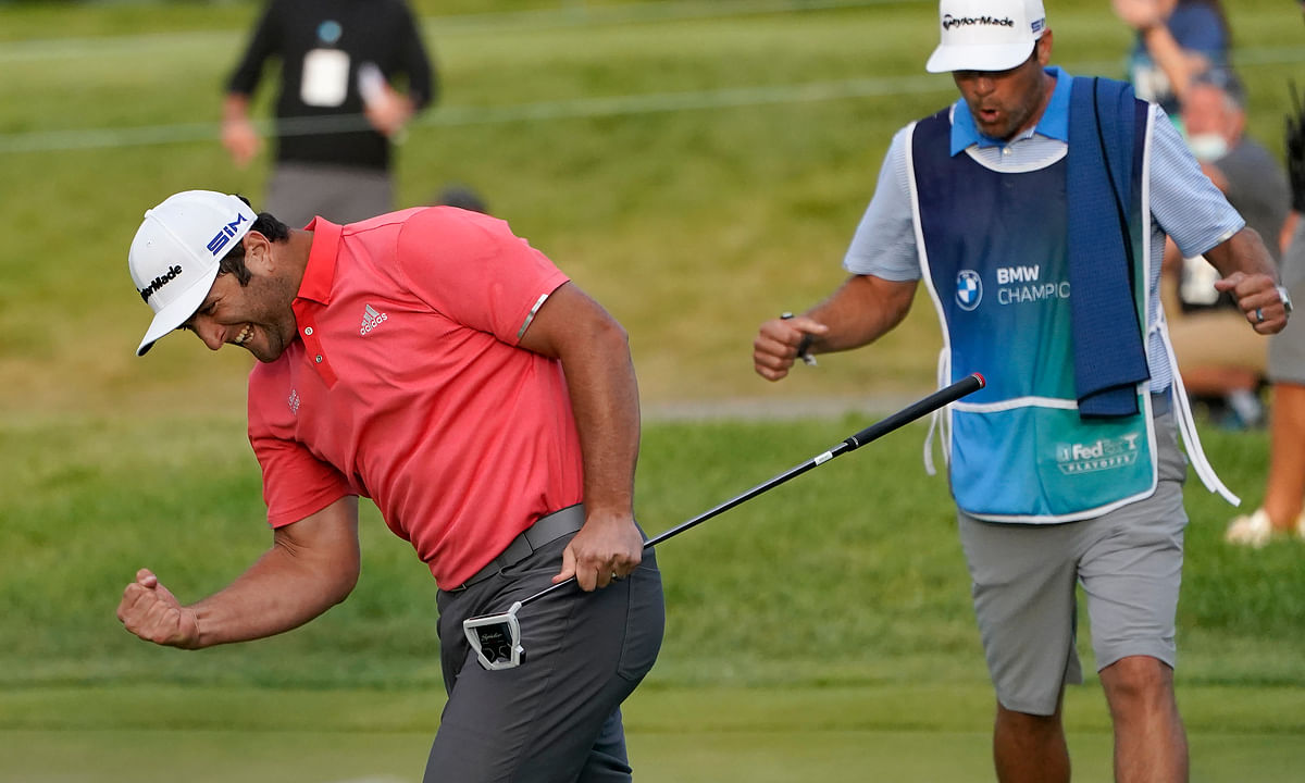 Jon Rahm, left, reacts after making his putt on the first playoff hole next to caddie Adam Hayes during the final round of the BMW Championship golf tournament at the Olympia Fields Country Club in Olympia Fields, Ill., Sunday, Aug. 30, 2020.
