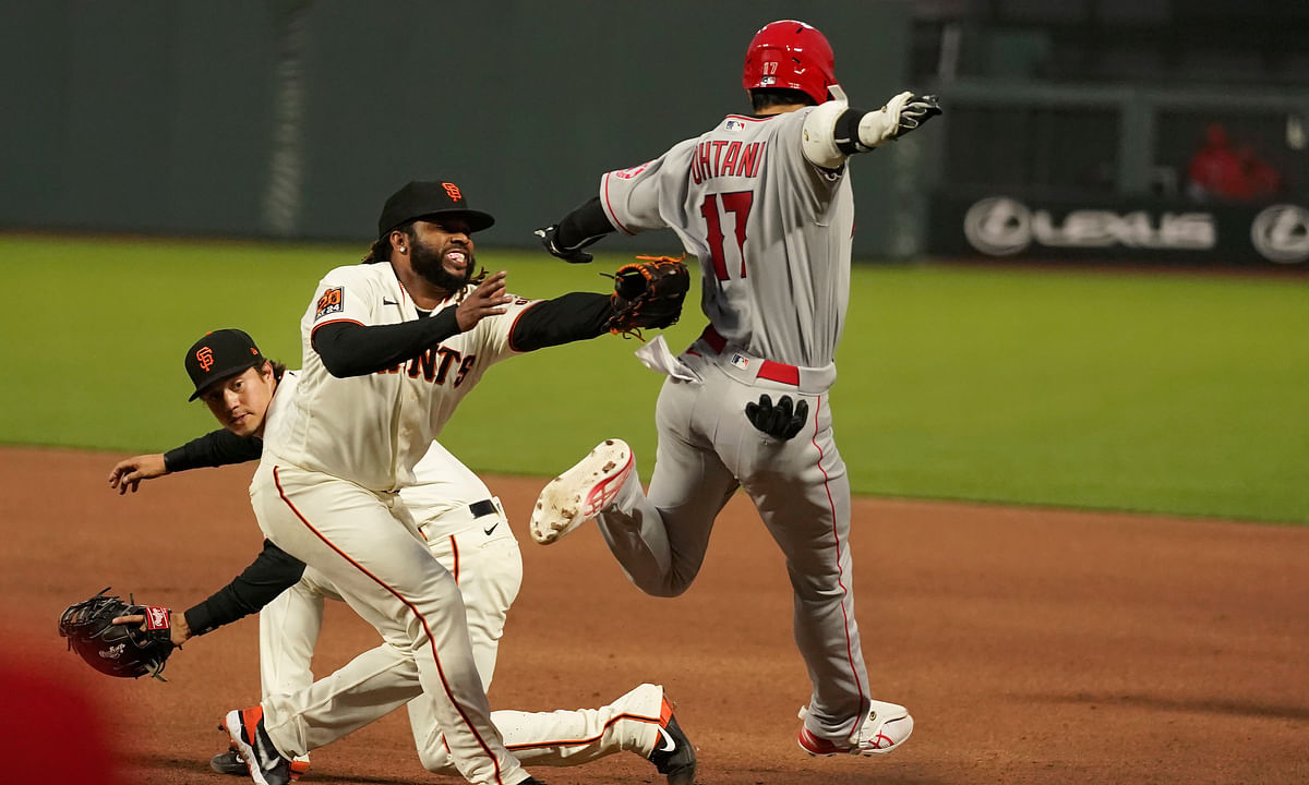 San Francisco Giants pitcher Johnny Cueto, center, reaches to tag out Los Angeles Angels' Shohei Ohtani (17) during the fourth inning of a baseball game in San Francisco, Wednesday, Aug. 19, 2020. At left rear is first baseman Wilmer Flores.