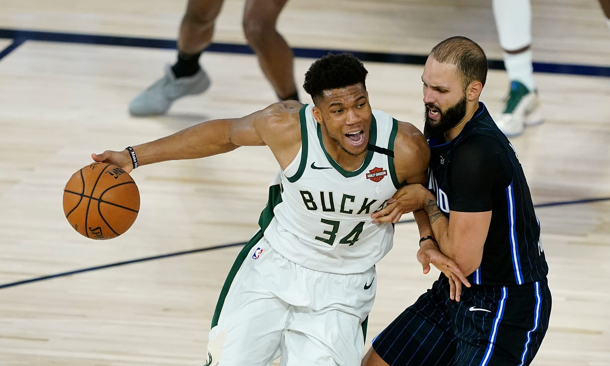 Milwaukee Bucks' Giannis Antetokounmpo drives past former  Orlando Magic player Evan Fournier.