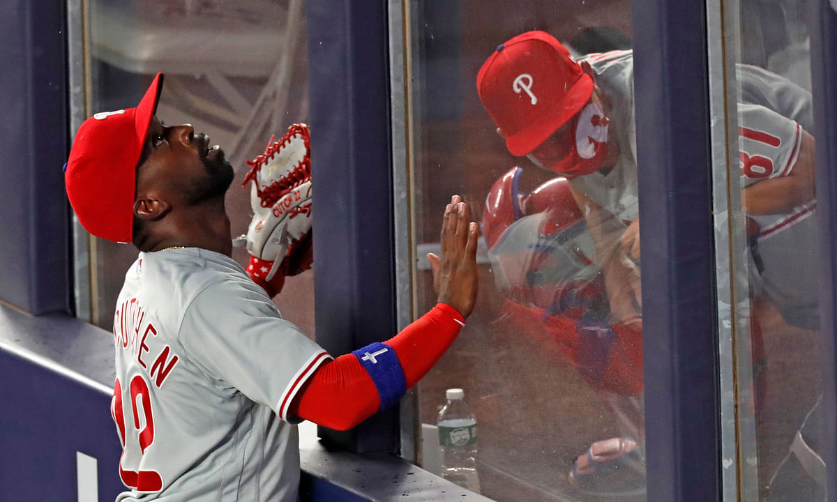 Philadelphia Phillies left fielder Andrew McCutchen (22) tracks the path of Gio Urshela's sixth-inning, three-run home run as Phillies catrching coach Greg Brodzinski ducks in the bullpen in a baseball game against the New York Yankees, Monday, Aug. 3, 2020, at Yankee Stadium in New York.