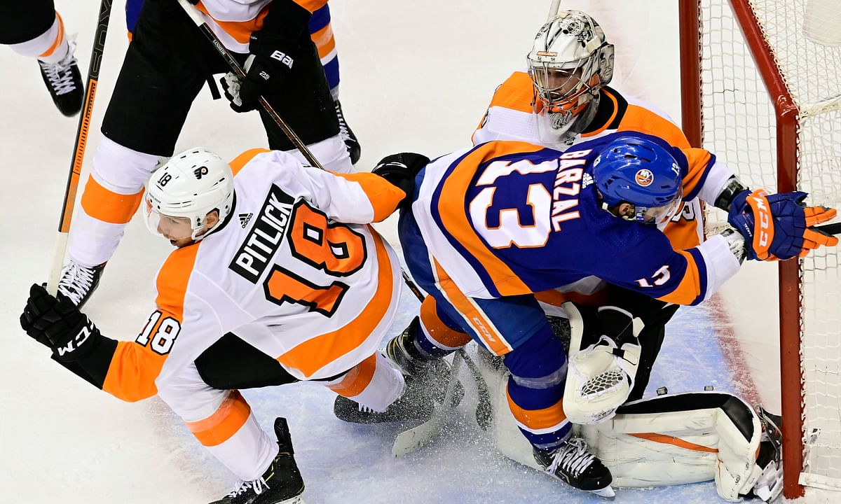Philadelphia Flyers right wing Tyler Pitlick (18) battles New York Islanders center Mathew Barzal (13) in front of Flyers goaltender Carter Hart (79) during second-period NHL Stanley Cup Eastern Conference playoff hockey game action in Toronto, Saturday, Aug. 29, 2020.