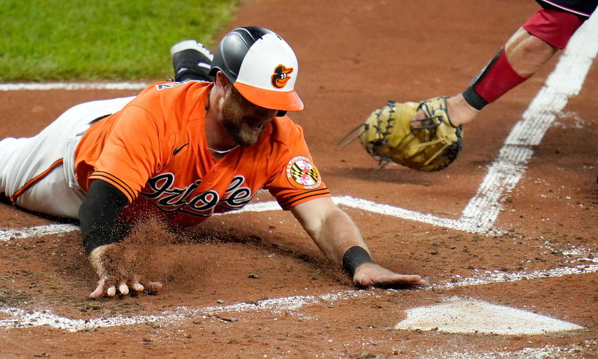 Baltimore Orioles' Bryan Holaday slides head first into home plate ahead of the tag of Washington Nationals catcher Yan Gomes while scoring on a triple by Orioles' Andrew Velazquez during the second inning of a baseball game, Saturday, Aug. 15, 2020, in Baltimore.
