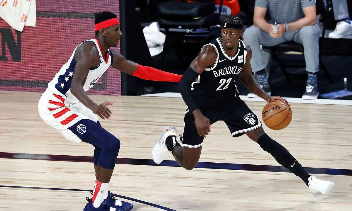 Brooklyn Nets guard Caris LeVert (22) dribbles against Washington Wizards forward Isaac Bonga (17) in the first half of an NBA basketball game Sunday, Aug. 2, 2020, in Lake Buena Vista, Fla.