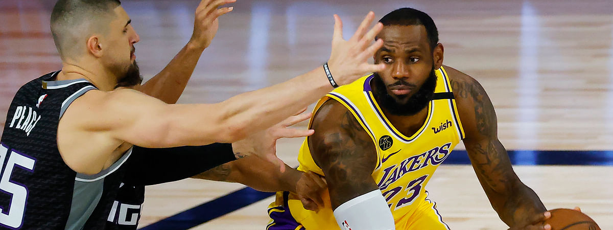 Los Angeles Lakers' LeBron James (23) is pressured by Sacramento Kings' Alex Len (25) during the first half of an NBA basketball game Thursday, Aug. 13, 2020, in Lake Buena Vista, Fla.