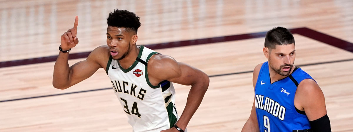 Milwaukee Bucks' Giannis Antetokounmpo (34) celebrates after a dunk as Orlando Magic's Nikola Vucevic (9) looks back during the first half of an NBA basketball first round playoff game Saturday, Aug. 29, 2020, in Lake Buena Vista, Fla.