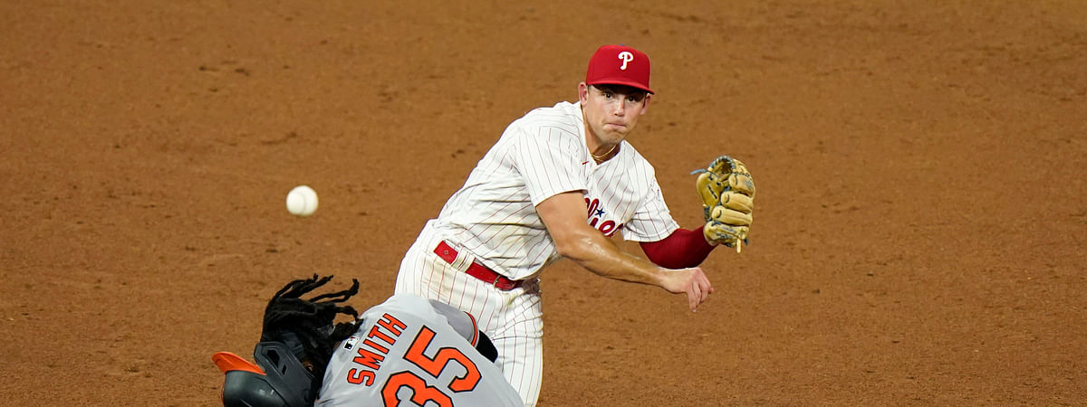 Philadelphia Phillies' second baseman Scott Kingery, top, throws to first after forcing out Baltimore Orioles' Dwight Smith Jr. at second on a fielder's choice by Austin Hays during the sixth inning of a baseball game, Tuesday, Aug. 11, 2020, in Philadelphia. Hays was safe at first on the play.
